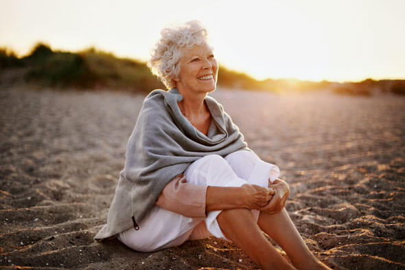elderly woman sitting on the beach
